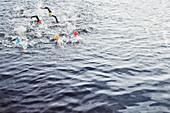 Triathletes splashing in water
