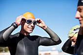 Triathlete adjusting goggles outdoors