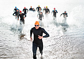 Triathletes emerging from water