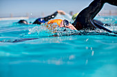 Triathletes in wetsuit splashing in pool