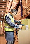 Worker scanning box in warehouse