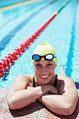 Smiling swimmer leaning at edge of pool