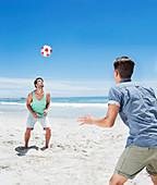 Man heading soccer ball on beach