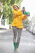 Woman emptying boot in rain