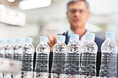 Supervisor examining bottles in factory