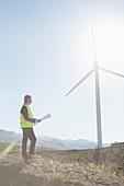 Businessman examining wind turbine