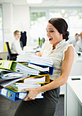 Businesswoman carrying folders in office