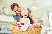 Father carrying baby in laundry basket