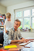 Boy distracting father at work