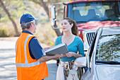Roadside mechanic talking with woman
