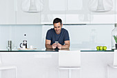 Man using cell phone in modern kitchen