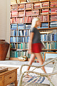Blurred view of woman walking by bookcase
