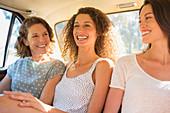 Three women sitting in car backseat