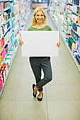 Woman holding blank card aisle