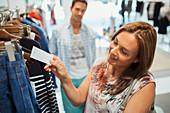 Woman checking tag while shopping