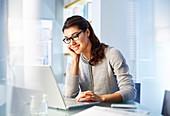 Female office worker sitting using laptop