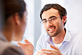 Smiling man in glasses with client