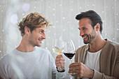 Smiling men toasting wine glasses