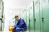 Worker holding hard-hat in locker room