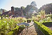 Wheelbarrow in sunny formal garden