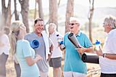 Yoga instructor talking to senior men