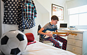 Boy playing electric guitar in bedroom