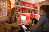 Girls playing guitar and using tablet