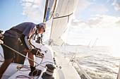 Retired man sailing on sunny ocean