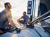 Men monitoring wind on sailboat