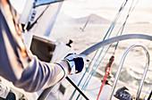 Man sailing steering sailboat at helm