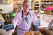 Portrait Worker behind desserts in market