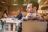 Pensive man drinking coffee at laptop