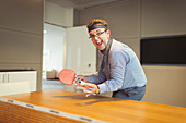 Businessman playing ping pong in conference room