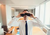 Businessman using binoculars in conference room