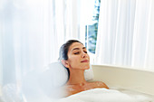 Serene woman enjoying bubble bath with eyes closed