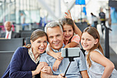 Family taking selfie with selfie stick at airport