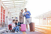 Family with suitcases waiting platform