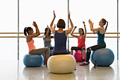 Women on fitness balls cheering and clapping