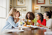 Smiling women drinking coffee and talking