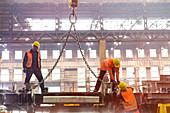 Steel workers fastening crane chain in factory