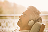 Serene man with headphones on sunny patio