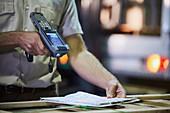 Worker with scanner scanning paperwork