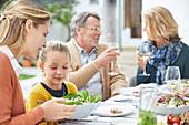 Multi-generation family enjoying lunch on patio