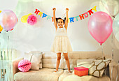 Girl with arms raised on sofa at birthday party