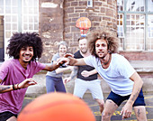 Friends playing basketball at basketball court