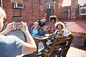 Woman photographing friends hanging out on rooftop
