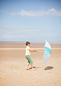 Wind pulling umbrella in hands of boy