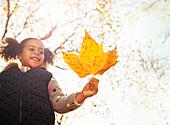 Smiling girl holding orange maple leaf