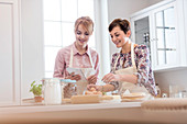 Female caterers with tablet baking