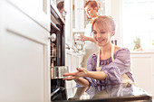 Smiling woman baking, placing cake in oven